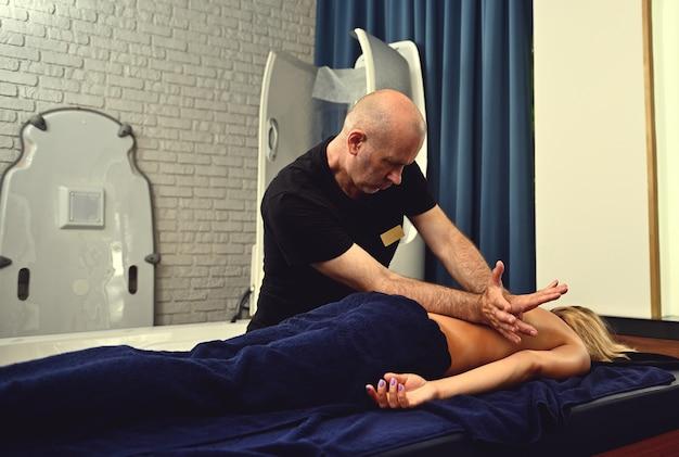 Choropraktiker, der therapeutische heilkörpermassage für junge patienten durchführt, die auf einem massagetisch im modernen wellnesscenter liegen.