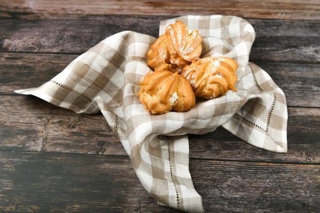 Choux-kuchen auf einem holz. in einem korb auf einem karierten handtuch. die wohnung lag. . schick mit quark. kleine vanillepuddingkuchen in weidenschale auf holz