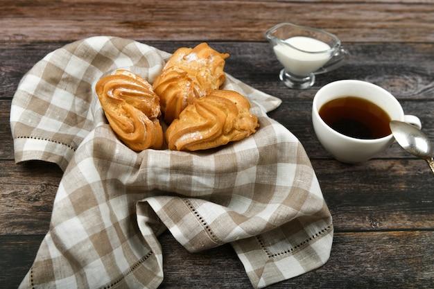 Choux-kuchen mit kaffee auf einem holz. in einem korb auf einem karierten handtuch. . schick mit quark. kleine vanillepuddingkuchen in weidenschale auf holz