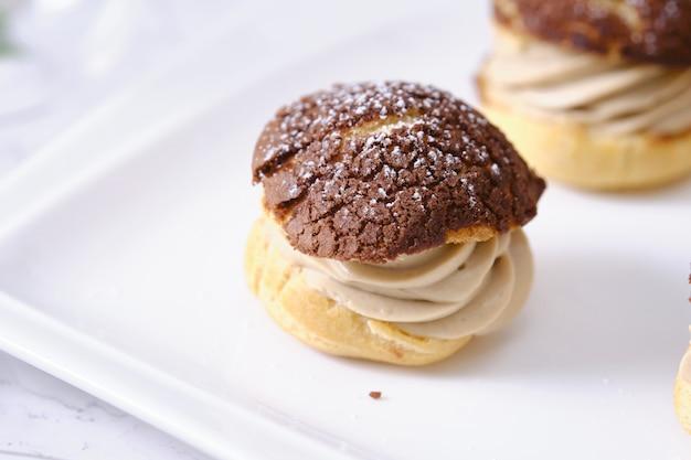 Choux-sahne oder windbeutel oder französische kränzchen mit frischer sahne auf dem kaffeetisch.