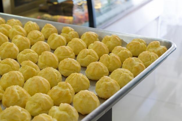 Chouxcreme im bäckereibehälter auf tabelle.