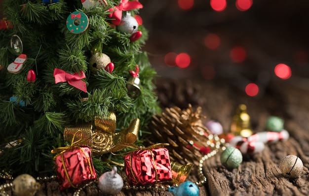 Chrismas-baum mit geschenk auf altem hölzernem und rotem hellem bokeh, fröhlichen chrismas und guten rutsch ins neue jahr-konzept
