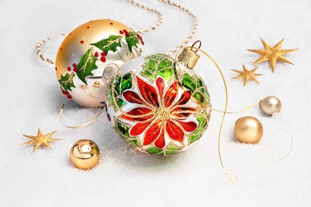 Christbaumkugeln mit weihnachtsstern design und goldenen dekorationen auf schnee
