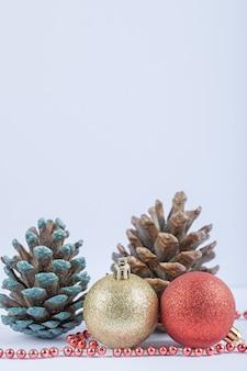Christbaumkugeln und eichenzapfen mit roter perlenkette auf dem weiß