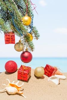 Christbaumschmuck am strand in tropischen. neujahrsurlaub in heißen ländern