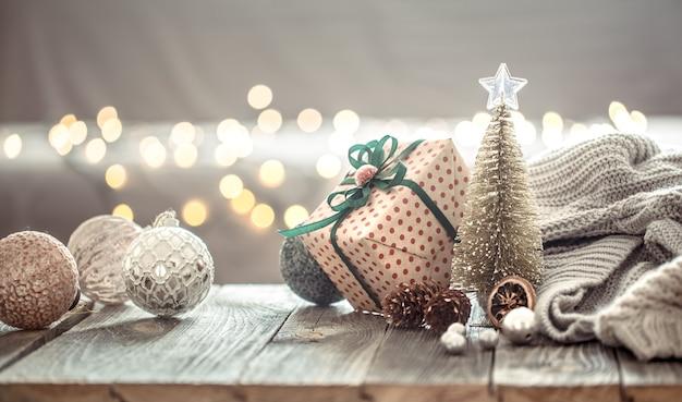 Christbaumschmuck über weihnachtslichter bokeh im haus auf holztisch mit pullover an einer wand und dekorationen.