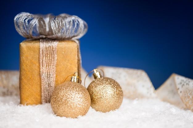 Christbaumschmuck und geschenk auf schnee vor blauem hintergrund