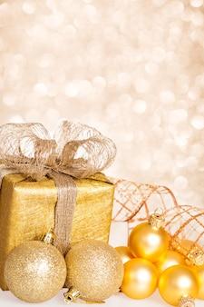Christbaumschmuck und geschenkbox gegen lichterhintergrund