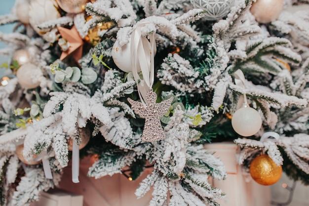 Christbaumschmuck. verschiedene weihnachtsverzierungen, engel, bälle, schneeflocken auf dem baum. weihnachtsdekorationen .