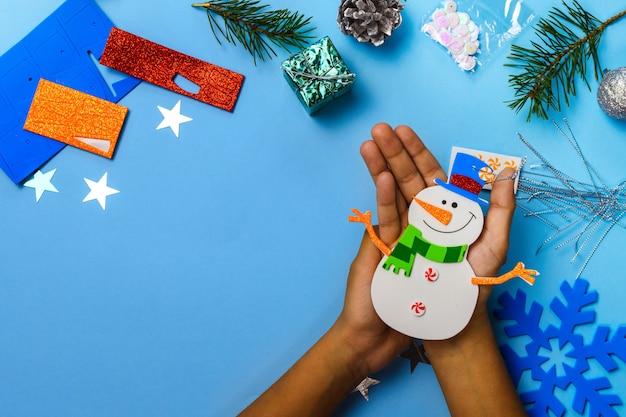Christbaumschmuck zum aufhängen. schneemannteile auf blauem hölzernem hintergrund. bastelideen zu weihnachten. ansicht von oben. nahaufnahme. heimwerken.
