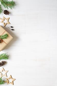 Christbaumzweigkegel und hölzernes weihnachtszubehör auf einem weißen hölzernen hintergrundrahmen kopieren raumzusammensetzung