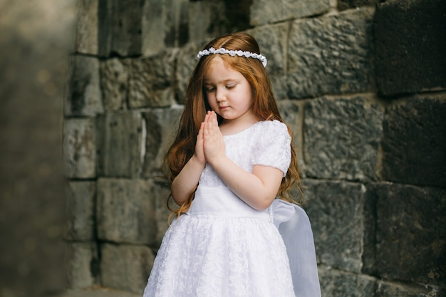 Christentum und spiritualität. entzückendes rothaariges mädchen mit weißem kleid, das vor armenischer alter kirche betet