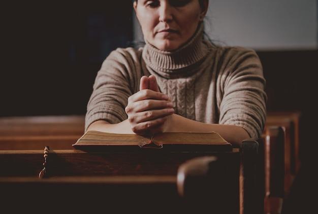 Christliche frau, die in der kirche betet. hände gekreuzt und bibel auf holzschreibtisch.