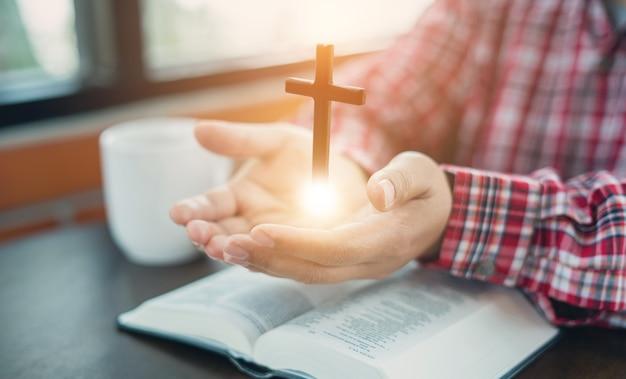 Christliche hand beim beten und anbeten für die christliche religion mit unschärfe ihres körperhintergrunds, gelegenheitsmann, der mit ihren händen zusammen über einer geschlossenen bibel betet. christlicher hintergrund. freiheit.