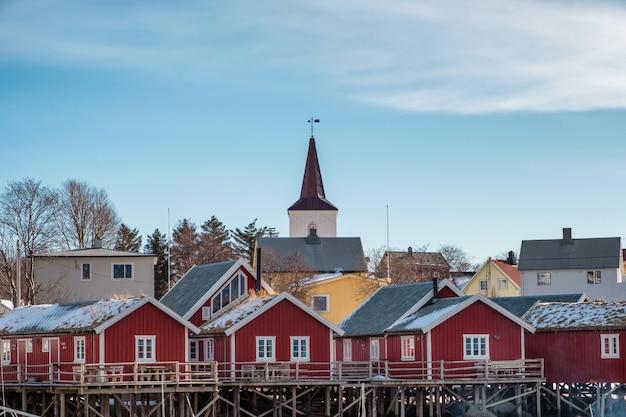 Christliche kirche auf rotem fischerdorf an der küstenlinie