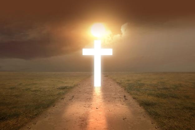 Christliches kreuz auf der schmutzigen straße mit einem sonnenuntergangshimmelhintergrund