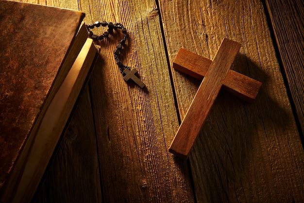 Christliches kreuz auf hölzerner bibel und rosenbeet