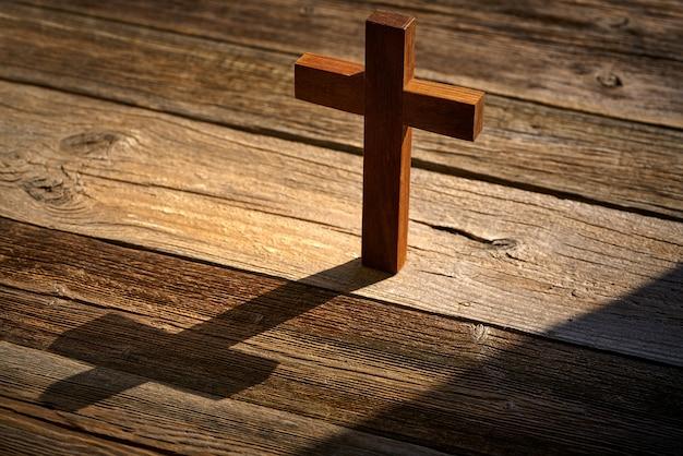 Christliches kreuz auf holz über hölzernem