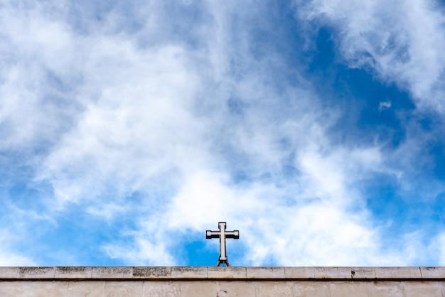 Christliches kreuz oben auf eine kirche mit vielem kopienraum des blauen himmels.