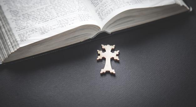 Christliches kreuz und bibel auf dem schwarzen tisch