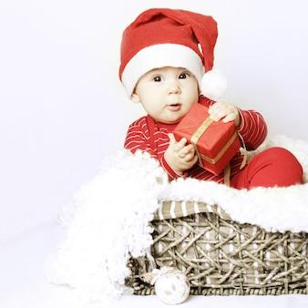 Christmasr baby tragen weihnachtsmütze und geschenk