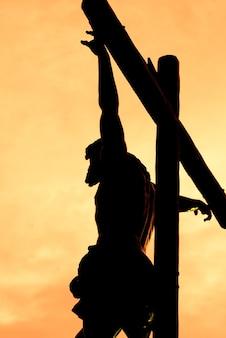 Christus kreuzigte gegen das licht während des sonnenuntergangs