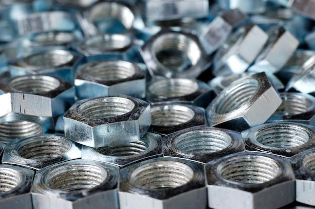 Chrom-metallmuttern in nahaufnahme in form von waben liegen nebeneinander und bilden einen bereich.