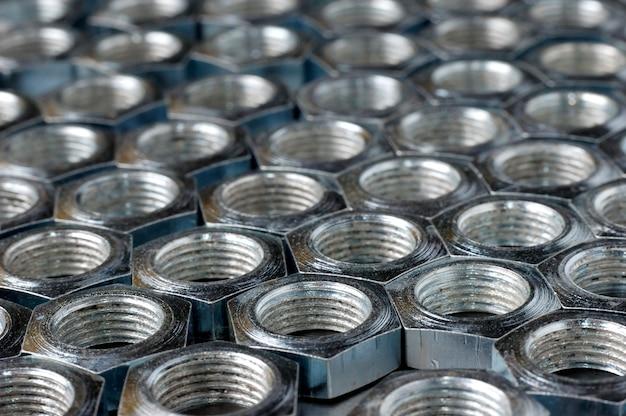 Chrom-metallmuttern in nahaufnahme in form von waben liegen nebeneinander und bilden einen bereich