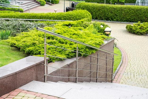 Chromgeländer mit stumpfen in einem mehrstufigen park im landschaftsdesign