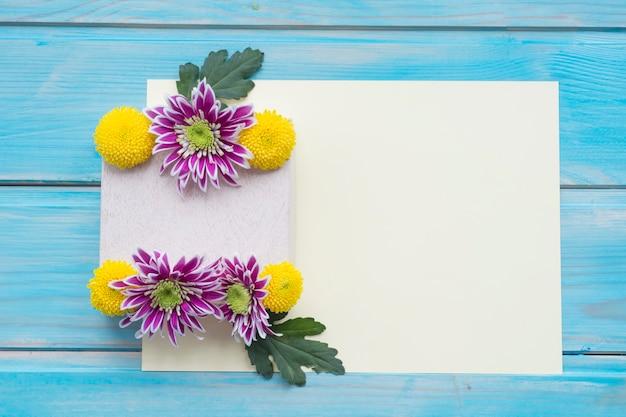 Chrysantheme blüht über dem leeren papier auf blauem holztisch
