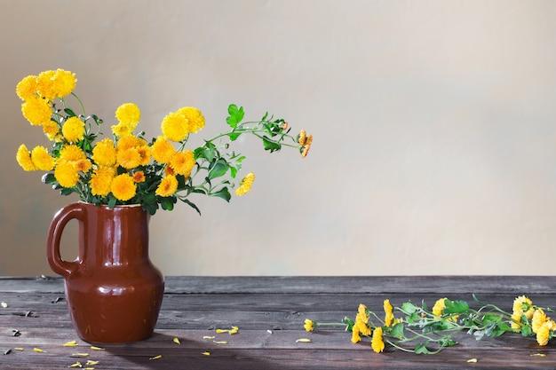 Chrysanthemen in vase auf altem holztisch