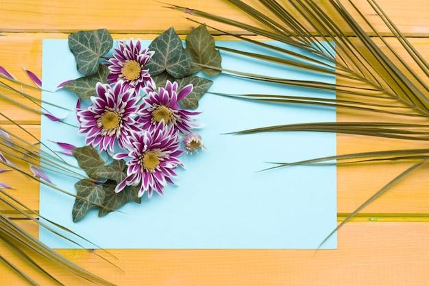 Chrysanthemenblume mit efeu- und palmblättern auf leerem papier über dem hölzernen hintergrund