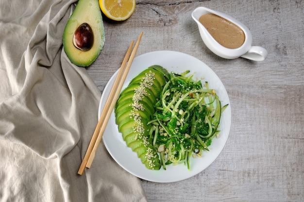 Chukka-salat, gurkennudeln mit avocado und erdnussbrauner sauce im sauciere