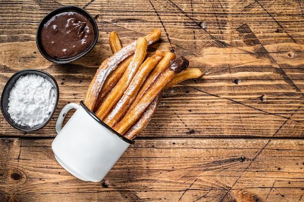 Churros mit zucker und schokoladensauce. hölzern