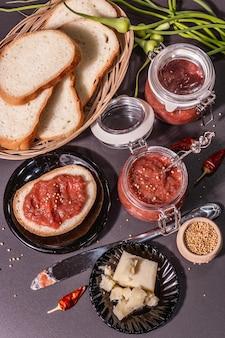 Chutney aus rhabarber. zutaten für ein gesundes frühstück. schwarzer steinbetonhintergrund, trendiges hartes licht, dunkler schatten, draufsicht