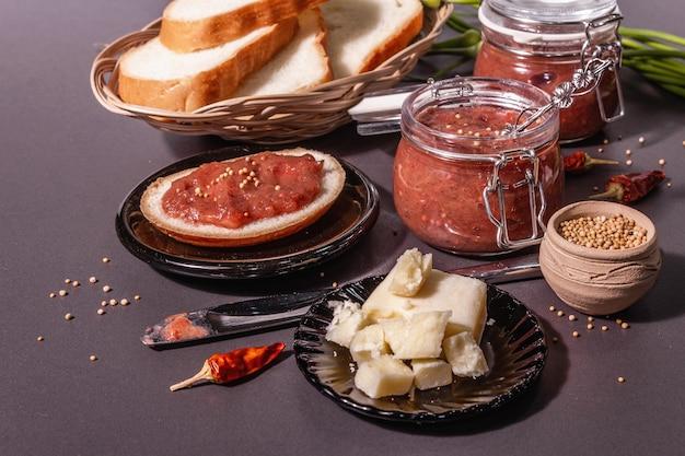 Chutney aus rhabarber. zutaten für ein gesundes frühstück. schwarzer steinbetonhintergrund, trendiges hartes licht, dunkler schatten, nahaufnahme