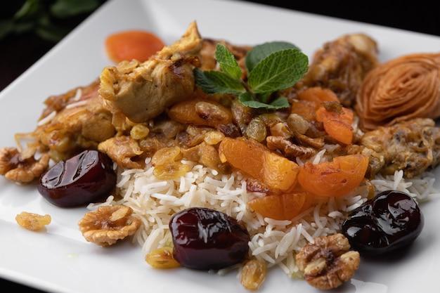 Chyhyrtma-pilaw mit lammfleisch, getrockneten früchten, datteln und walnüssen auf einem weißen teller