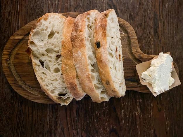 Ciabatta mit geräucherter butter wird auf einem holzstab in stücke geschnitten