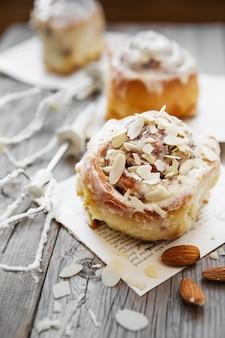 Cinnabon-brötchen mit frischkäse und sahne, schokolade und mandelnüssen auf holz