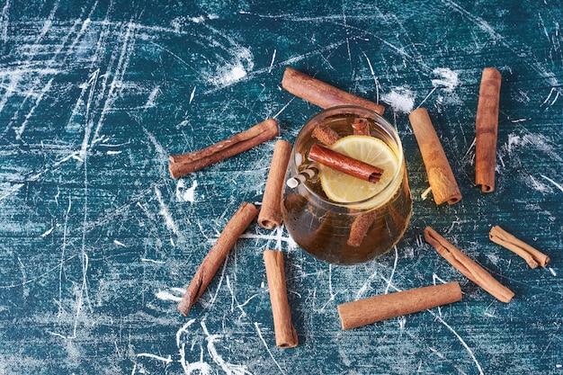 Cinnamonnd zitronen mit einer tasse getränk auf blau.