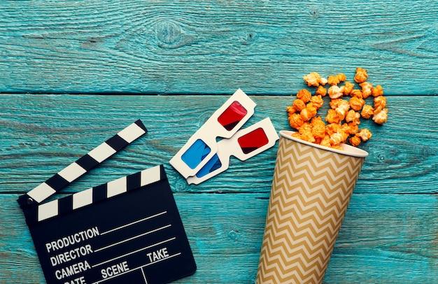 Clapperboard, gläser und popcorn auf draufsicht des blauen hölzernen hintergrundes mit copyspace
