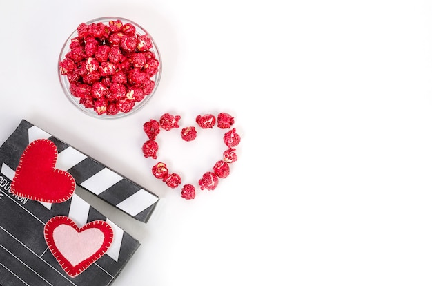 Clapperboard mit herzen und rotem karamellpopcorn