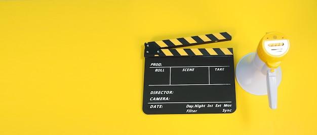Clapperboard oder filmklapperbrett in gelber und schwarzer farbe und megaphon einzeln auf gelbem hintergrund. es usd in der kino-, film- und videoproduktion.