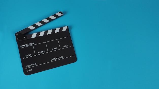 Clapperboard oder movie slate. es wird in der videoproduktion, film- und kinoindustrie auf blauem hintergrund verwendet.
