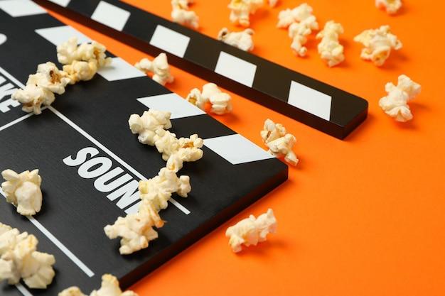 Clapperboard und popcorn auf orangefarbenem raum. essen zum kino gucken