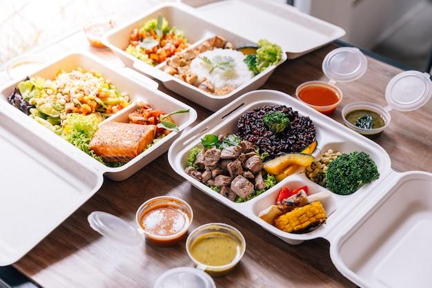 Clean-food-mahlzeit-box: gewürfeltes gegrilltes rindfleisch serviert mit reis-beere und gegrilltem gemüse.