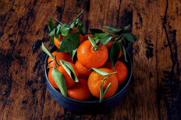 Clementinen mit blättern in einer blauen keramikschale auf einem alten holztisch