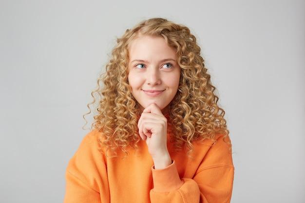 Clever lächelt nachdenkliches blondes mädchen nachdenklich