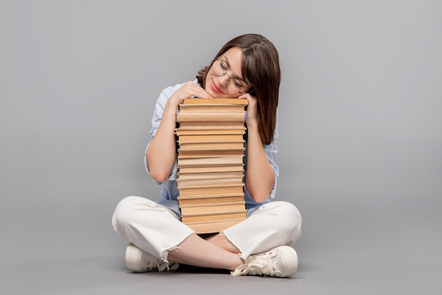 Clevere studentin oder bibliothekarin mit gekreuzten beinen, die ihren kopf auf büchern hält und davon träumt, sie alle zu lesen