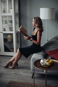 Clevere und schöne frau, die nach einem harten arbeitstag ein buch liest